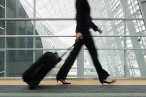Business woman walking through airport with suitcase